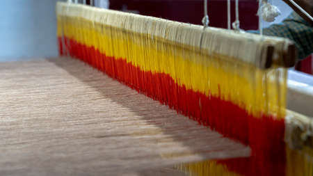 A worker working on woollen cloth showing hand weaving in a handloom textile factory from North India Stock Photo