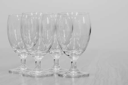 black and white empty wine glasses lined up on a brown wooden table Is a product show.