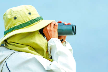 Bird watchers that blend in with nature look for something with binoculars. On a blue sky day. Foto de archivo