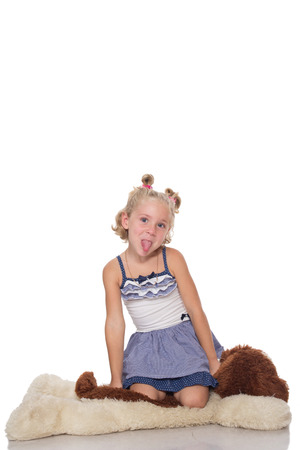 Cute little blonde girl sitting on a big soft dog toy on white background