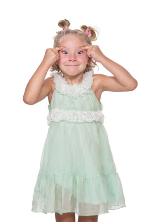 Little girl making funny face, on a white background, isolated photo