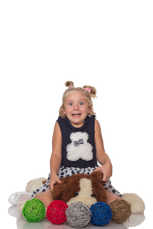 Cute little blonde girl sitting on a big soft dog toy on white background photo