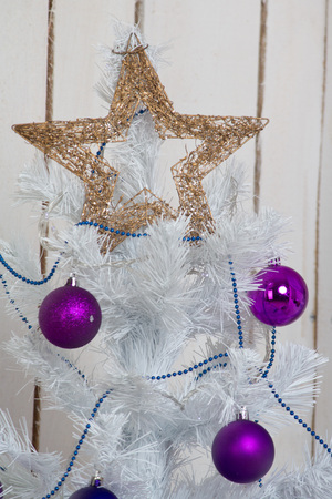 White Christmas tree with purple ornaments, balls and star Stockfoto