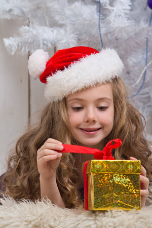 Little girl with christmas present in front of fir tree