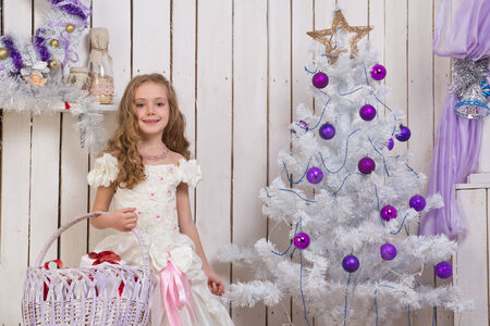 Little girl over christmas fir tree with wicker basket of presents