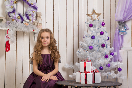 Little girl with christmas presents in front of fir tree