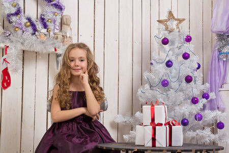 fir  tree: Little girl with christmas presents in front of fir tree