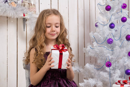 Little gLittle girl with christmas present in front of fir tree