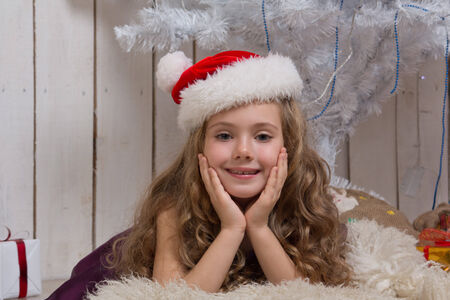 Little girl in Santa Claus hat dreaming over christmas fir tree