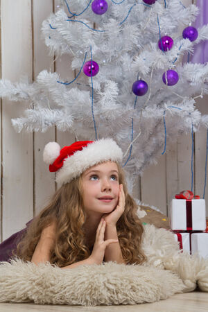 Little girl dreaming in front of fir tree