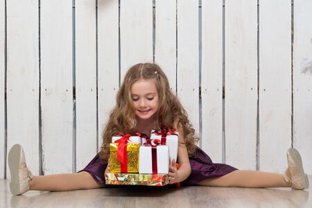 Happy little girl with gift boxes on wooden planks background