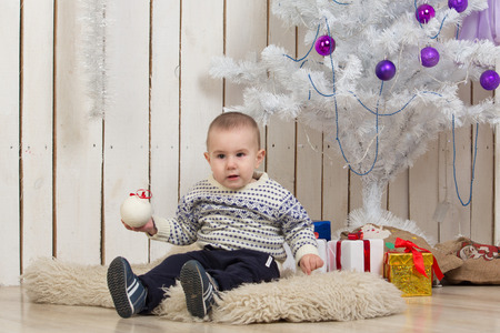 Baby boy under Christmas holiday fir tree with decorations and gifts