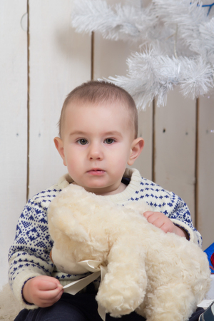 Baby boy under Christmas holiday fir tree with teddy bear Stockfoto