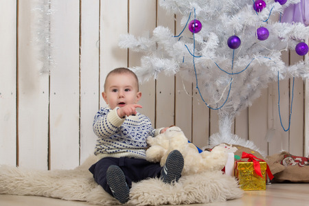Baby boy under Christmas holiday fir tree with gifts