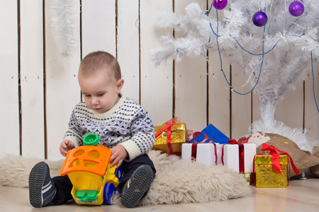 Baby boy under Christmas holiday fir tree with toy