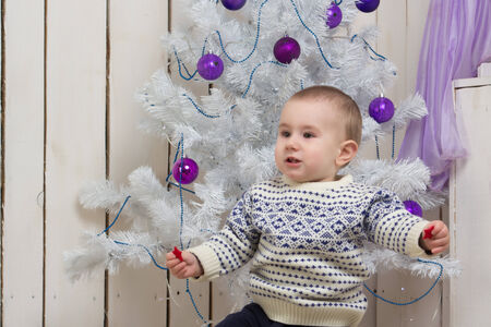 Baby boy under Christmas holiday fir tree with decorations