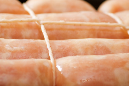 Raw chicken sausage covered with rope, close up Stockfoto