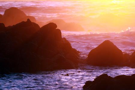 Background of sunset and waves crashing on rocky coastline near Monterey, California, USA