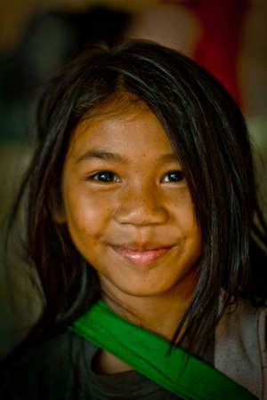 Angkor Wat, Cambodia - Febuary 24, 2012: Young local girl with smile selling curios