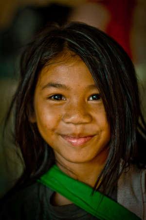angkor: Angkor Wat, Cambodia - Febuary 24, 2012: Young local girl with smile selling curios