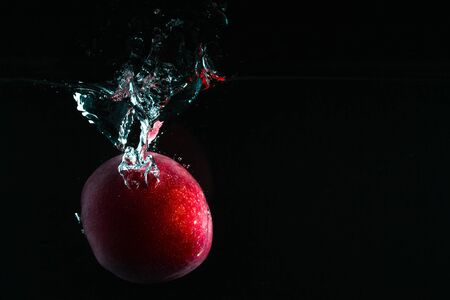 photo of object s: Splash photography: peach fruit on dark background