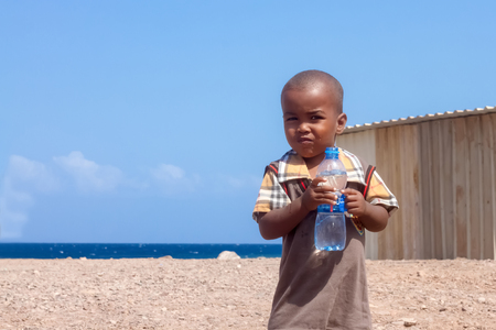 niños pobres: Niño Africano lindo con la botella de agua de bebida que sostiene en sus manos