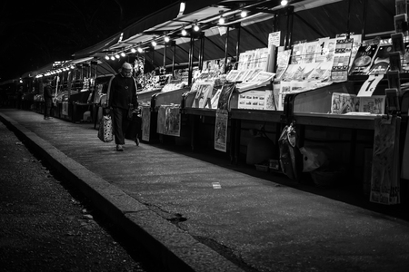 outcast: Rome, RomeItaly - October 17th 2015: Lonely and Pensive Black Man Walking Along an Empty Old Books Market in Rome Editorial
