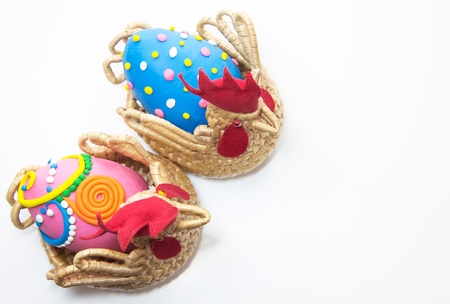 Two easter eggs in basket on white background