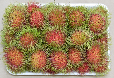 Rambutan on tray, tropical fruits Stock Photo
