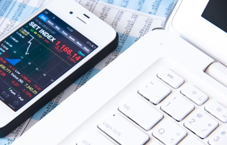 sell shares: Down stock on cell phone and escape computer keyboard Stock Photo