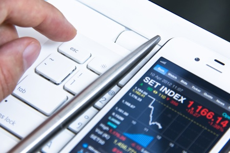 finger point to escape falling stock market from smartphone Stock Photo