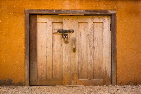 padlock and old metal hasp and wooden door