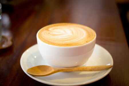 Close up white cup of cappuccino and spoon wood stands on dark wooden table