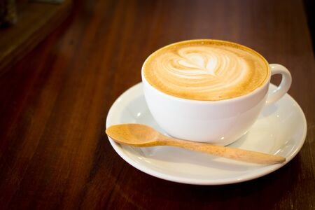 Close up white cup of cappuccino stands on dark wooden table Stock Photo