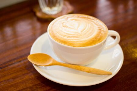 One white cup of cappuccino stands on dark wooden table Stock Photo