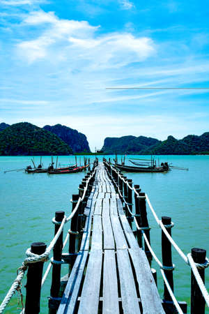 Old Wooden bridge into the sea.