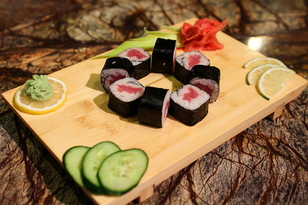 tekka: Delicious Tekka maki sushi rolls served with a wood plate.