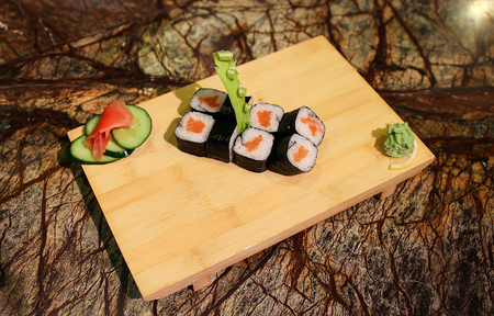 sake maki: Delicious Sake maki sushi rolls served with a wood plate.