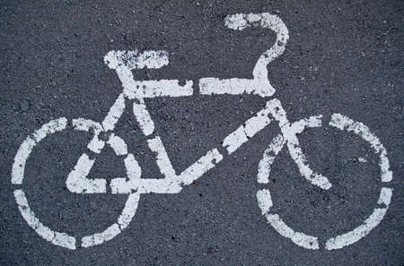 The sign of the cycle track on the asphalt, white faded paint.