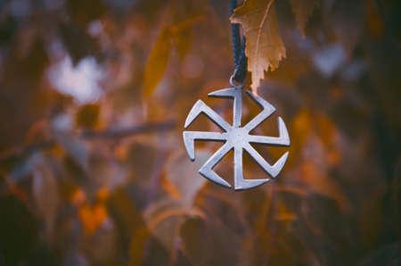 Symbol Kolovrat on the background of birch leaves.