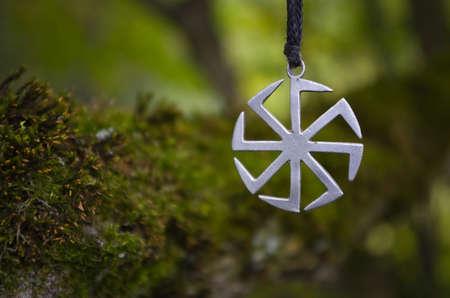 Pagan symbol Kolovrat on the background of moss.