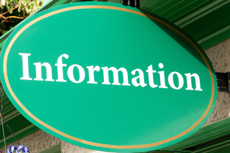A green wall sign with Tourism information
