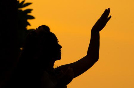 Silhouette of Backlit Hula dancer at Sun set, Hawaii Stock Photo