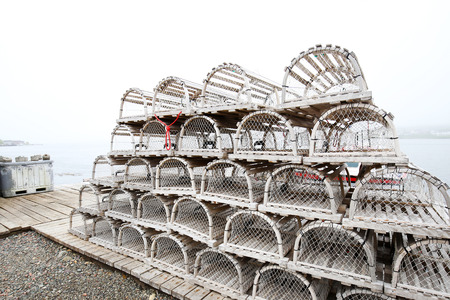 On a foggy day. Old style wooden lobster traps neatly piled at a Nova Scotia fishing village around Louisbourg, Nova Scotia, Canada.
