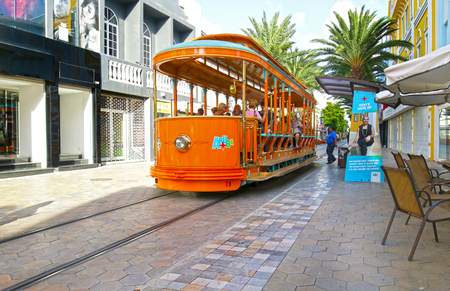 Oranjestad, Aruba - Oct 15, 2018.  Tourist boarding and riding on Free City Trolley / Street Car.  Hop on Hop Off in the tourist area. Editorial