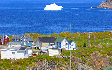 Iceberg in Harbour. Twillingate, Newfoundland, Canada. Maritime homes along the rugged cove shoreline in this coastal community, 写真素材