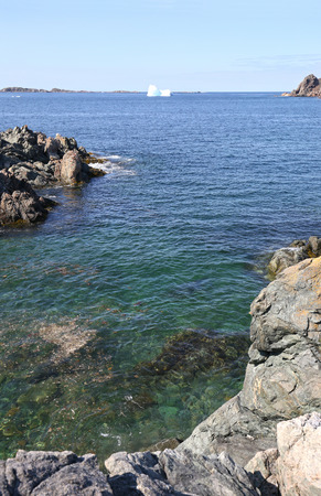 Iceberg close to shore. Twillingate, Newfoundland, Canada. Rugged Rocky cove shoreline in the foreground.