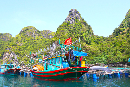 Halong Bay, Vietnam. Small Wooden Fishing boats docked at Floating Fishing village with Vietnam National Flag 写真素材