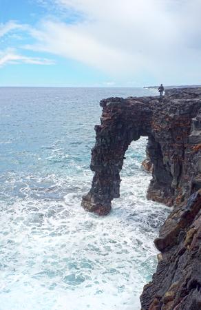 Turista caminando sobre Holei Sea Arch, Big Island, Parque Nacional de los Volcanes de Hawaii. Formación de arco de roca de lava