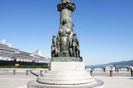 Trieste, Italy.  Popular Cruise Ship Port.  Ornaments at Base of Lamp Post at Piazza Unita di Italia (Unity of Italy Square). Main Focus on Statues in fore ground, cruise ship in background.